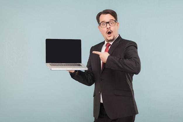 ビジネス、ガジェット、テクノロジー。新しいノートブックを示す驚きの顔を持つビジネスマン。屋内、スタジオショット、水色または灰色の背景に分離
