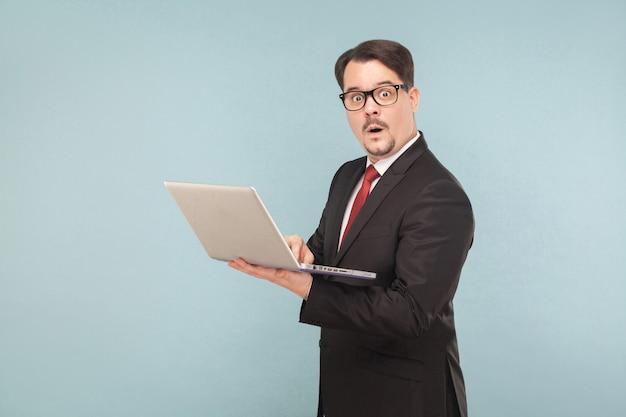 ビジネス、ガジェット、テクノロジー。ショックの男。ノートブックを持っています。屋内、スタジオショット、水色または灰色の背景に分離
