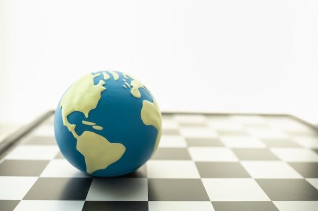 비즈니스, 게임 및 계획 개념입니다. 복사 공간이 있는 체스판에 있는 미니 세계 공의 근접 촬영.