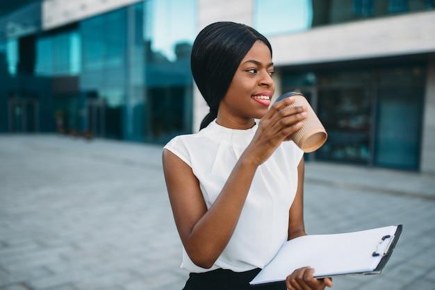 Деловая девушка скаливает кофе из картонной чашки