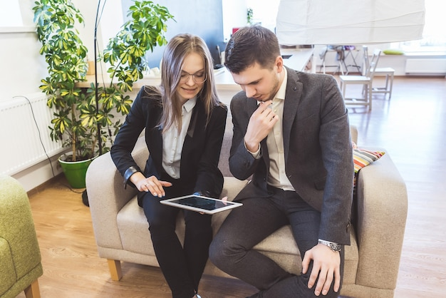 Business girl and guy looking at tablet, in office
