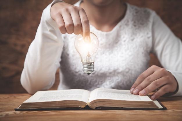 Деловая девушка держит лампочку. креативность