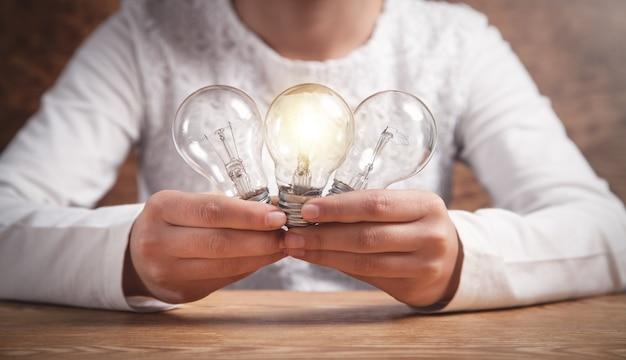 Девушка дела держа электрические лампочки. креативность