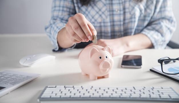 貯金箱にコインを置くビジネスの女の子。お金を節約