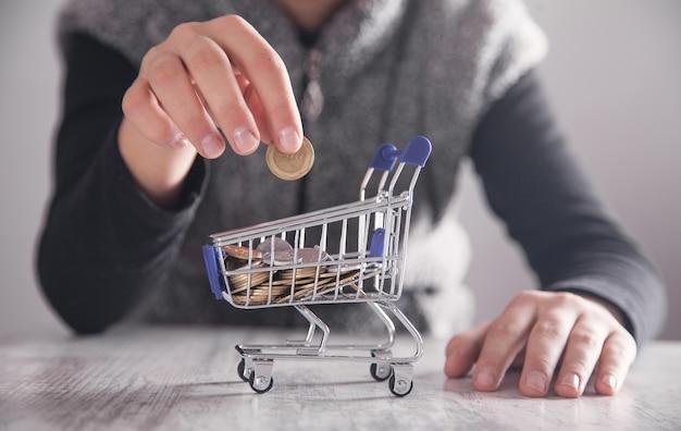 ショッピングカートにコインを置くビジネスの女の子。ショッピングのコンセプト