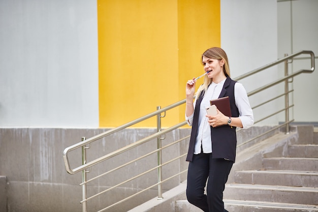 Business girl stands on the building steps and thinks