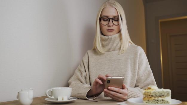 Деловая девушка с помощью мобильного телефона, сидя за столом