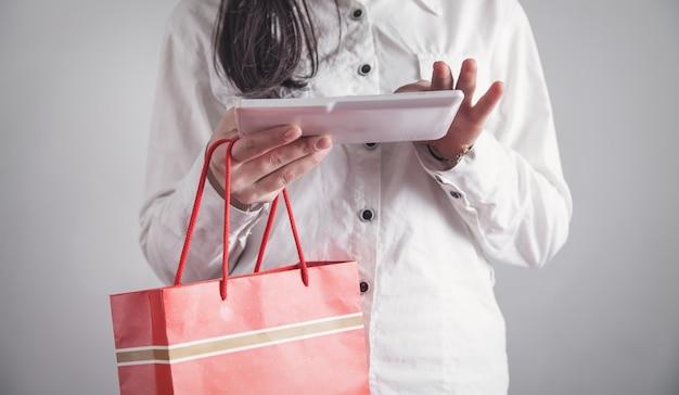태블릿을 사용 하 고 쇼핑백을 들고 비즈니스 소녀입니다.