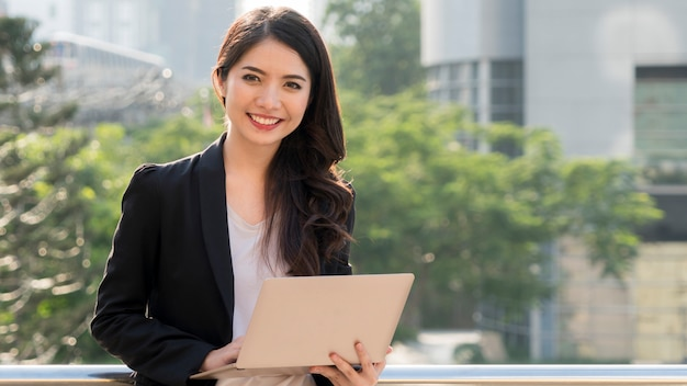 Business girl with computer notebook and city background.