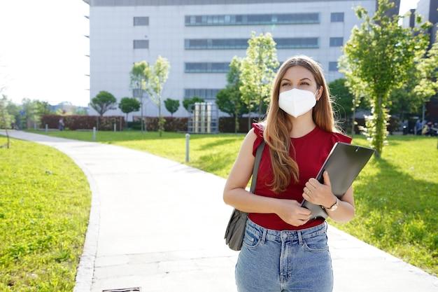 保護マスクを持つビジネスの女の子は、背景にオフィスビルと彼女の手でフォルダーを保持して歩きます
