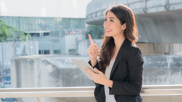 Business girl with smart tablet devices and city background.