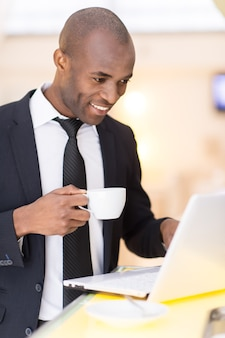 Business on the go. cheerful young african businessman using his laptop while standing at the bar