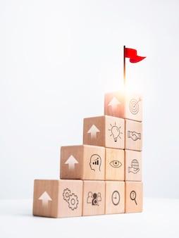 Бизнес-цель с процессом успеха роста для концепции лидерства. красный флаг на верхней части деревянных кубических блоков как ступенька со стрелкой вверх значок стратегии на белом фоне, вертикальный стиль.