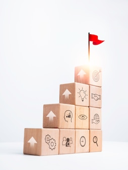 Business goal with growth success process for leadership concept. red flag on the top of wooden cube blocks as a stair step with up arrow sign strategy icon on white background, vertical style.