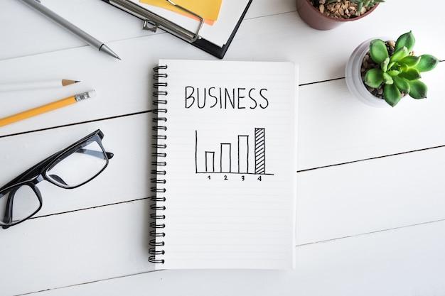 График бизнес-целей с блокнотом на офисном столе с принадлежностями и кактусом в горшке / вид сверху из белого дерева