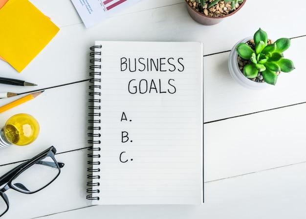 공급 및 냄비 선인장 / 상위 뷰 흰색 나무 배경이있는 사무실 책상 테이블에 메모장이있는 비즈니스 목표