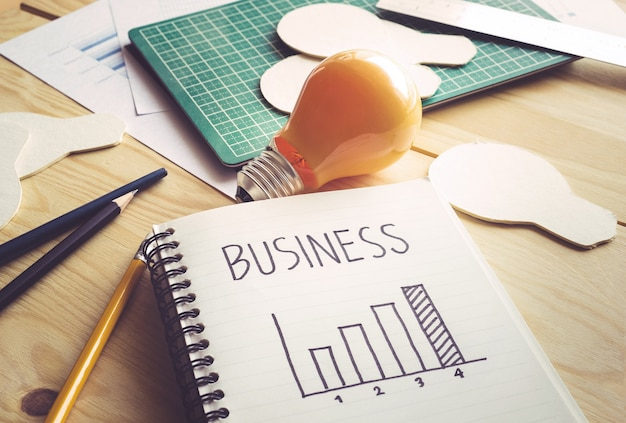 Business graph on notebook with lightbulb on wooden table.