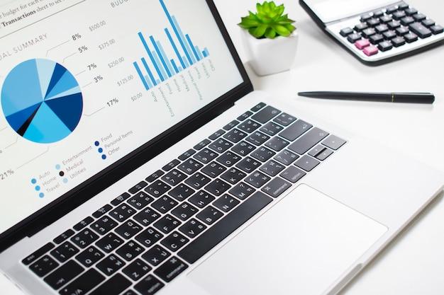 白いテーブル上のコンピュータ画面上のビジネスグラフ