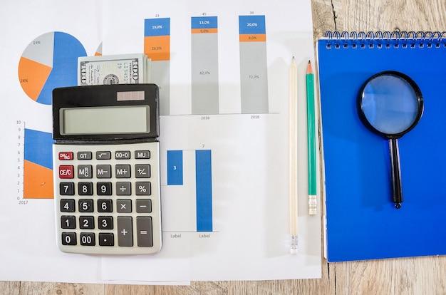 チャートのお金と計算機を備えたビジネスグラフ