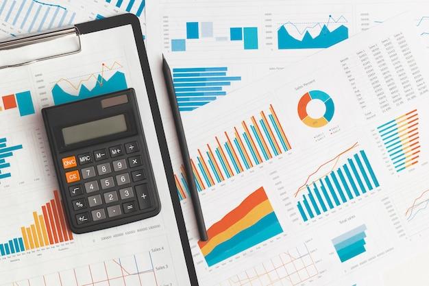テーブル上のビジネスグラフ、チャート、計算機。金融開発、銀行口座、統計
