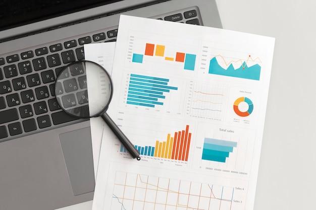 テーブルの上のビジネスグラフ、チャート、虫眼鏡。金融開発、銀行口座、統計