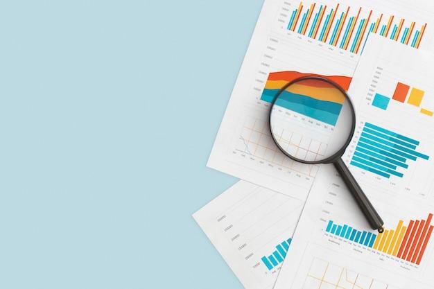 Бизнес-графики, диаграммы и увеличительное стекло на столе. финансовое развитие, банковский счет, статистика