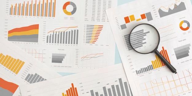 비즈니스 그래프, 차트 및 테이블에 돋보기. 금융개발, 은행계좌, 통계