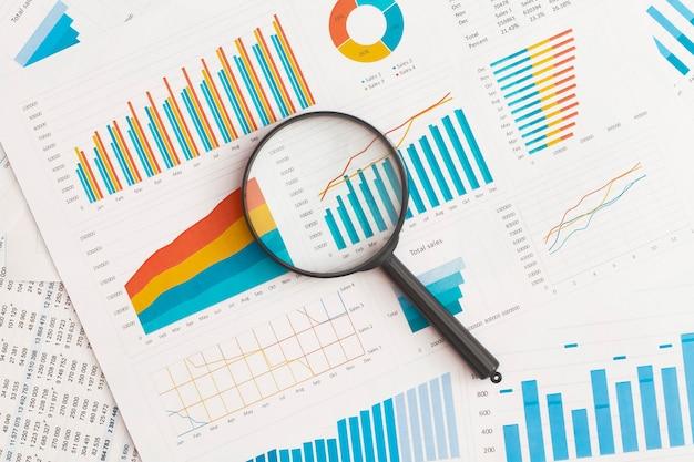 ビジネスグラフチャートとテーブル上の虫眼鏡財務開発