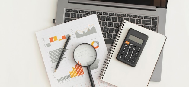 Business graphs, charts, laptop, magnifying glass and calculator on table. financial development, banking account, statistics