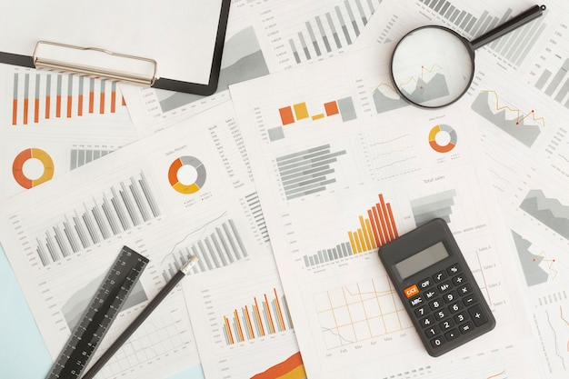 Business graphs, charts, magnifying glass and calculator on table. financial development, banking account, statistics