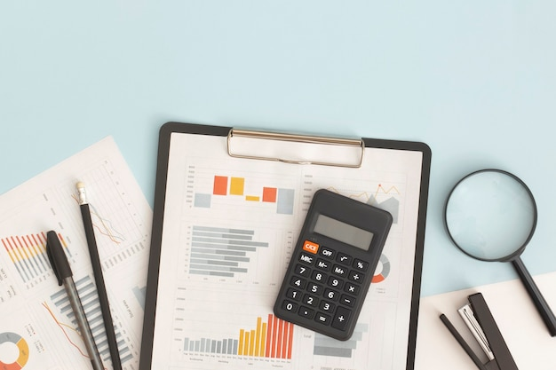 Business graphs charts magnifying glass and calculator on table financial development