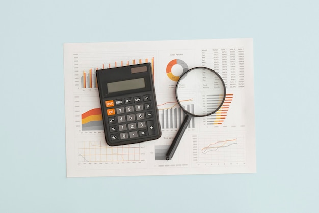 Business graphs charts and magnifying glass on table financial development