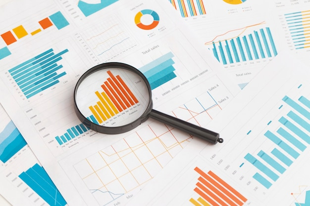 Business graphs charts and magnifying glass on table