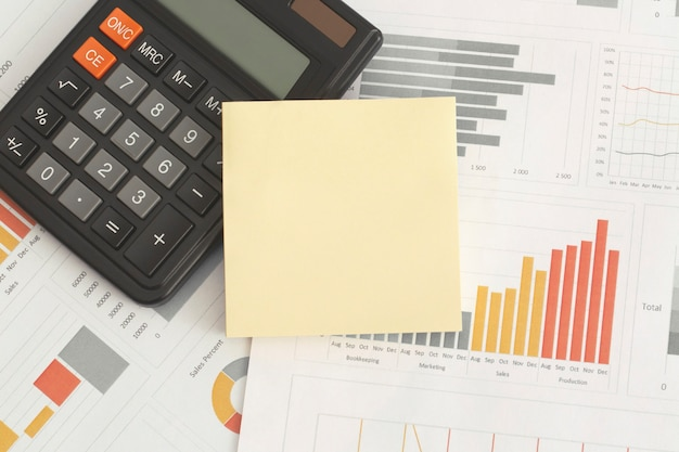 Business graphs charts sticky notes and calculator on table financial development