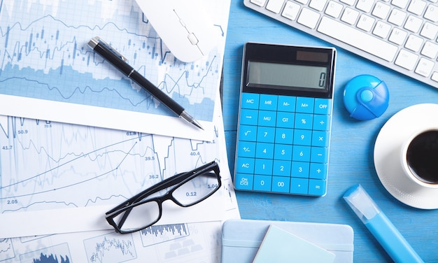 Business graphs, computer keyboard, mouse, coffee, pen, eyeglasses. business. analysis. accounting