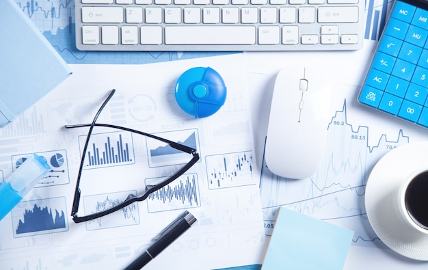Business graphs, computer keyboard, mouse, coffee, pen and eyeglasses