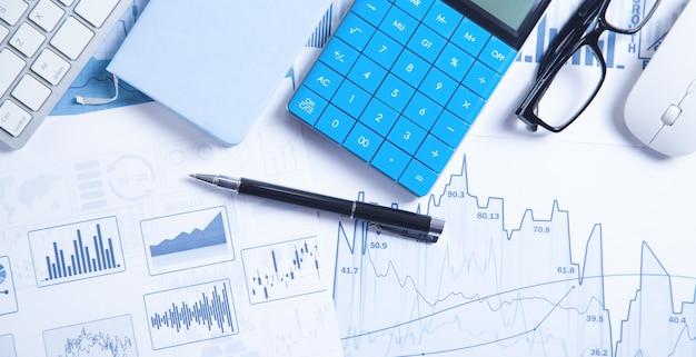 Бизнес-графики, компьютерная клавиатура, ручка, очки. бизнес. анализ. бухгалтерия