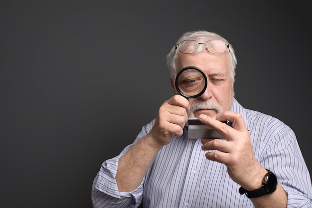 Business, grizzled man looks at a bank card through a magnifying glass