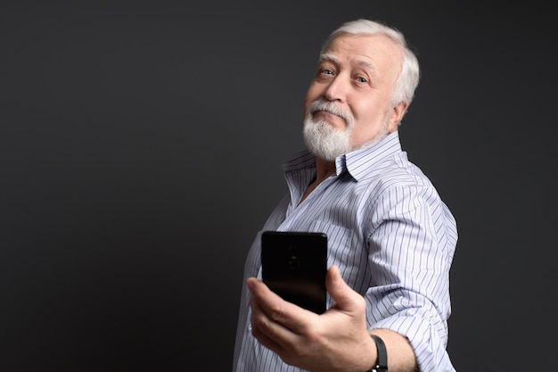 Business, grizzled man posing makes selfie on smartphone