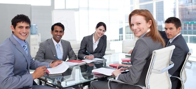 カメラで笑顔の民族の多様性を示すビジネスグループ