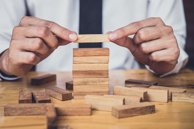 Business growth concept with wooden blocks, hand has piling up and stacking a wooden