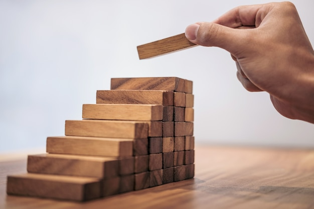 Business growth concept with wooden blocks, hand of man has piling up and stacking a woode