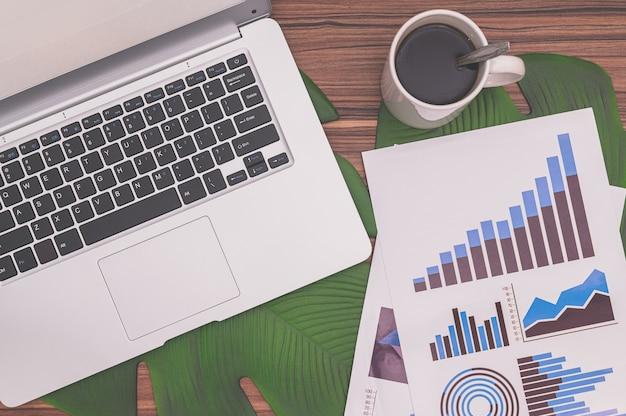 비즈니스 성장 그래프 문서 및 컴퓨터 커피 잔