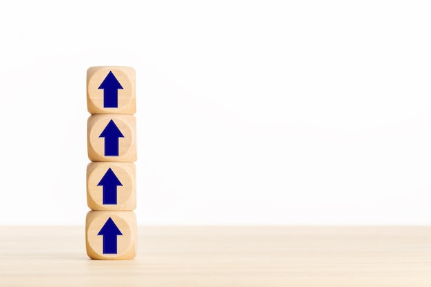 Business growth process concept. pile of wooden blocks with arrow pointing up.