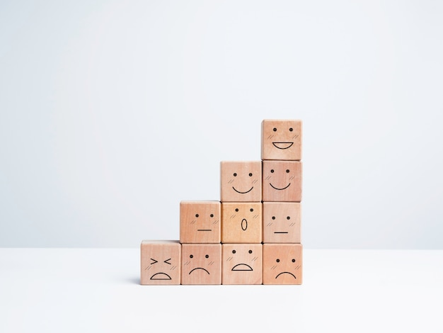 Business growth steps with happy and sad emotions on emoticon faces arrange on wooden blocks isolated on white background, minimal style. satisfaction, evaluation, rating survey concept.