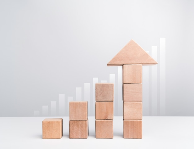 ビジネスの成長の成功の概念。上向きの矢印として積み重ねられた木製のブロックは、白い背景、最小限のエコスタイルの成長グラフチャートとして平均化されます。
