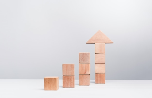 Business growth success concept. wooden blocks stacking as an arrow up averages as a growth graph chart on white background, minimal and eco style.