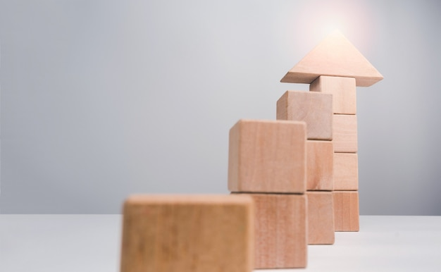 Business growth success concept. wooden blocks stacking as an arrow up averages as a growth graph chart on white background with copy space, minimal and eco style.