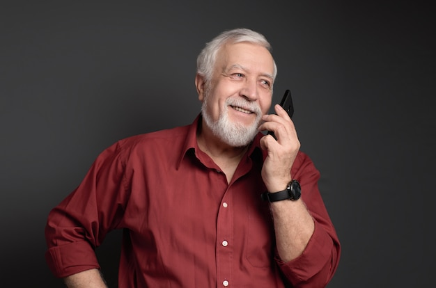Business-haired, gray-haired man in a red shirt is talking to the phone and laughing