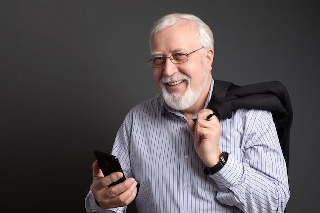 Business-haired, grizzled man in glasses with a phone smiles friendly